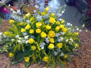 Composizione di rose gialle e delphinium azzurro